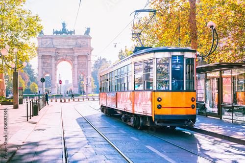 Poster Milan Famous vintage tram in the centre of the Old Town of Milan in the sunny day, Lombardia, Italy. Arch of Peace, or Arco della Pace on the background.