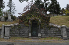 Old Stone Mausoleum Overgrown With Ivy In A Cemetery