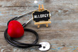 A board with the word allergy and stethoscope. The concept of medicine. A board with the word allergy and a stethoscope with a heart