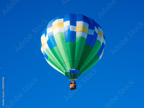 Colorful hot air balloon flying in the bright blue sky during Winthrop Balloon Festival in Washington state
