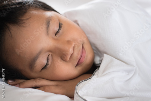 9ae9724ac boy sleeping with smile face on white bed sheet and pillow.boy fall asleep  with