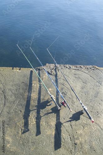 Fotografía  Three fishing rods on the coast of sea