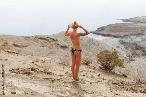 Photo Young topless girl in bikini standing above beach and ocean and posing