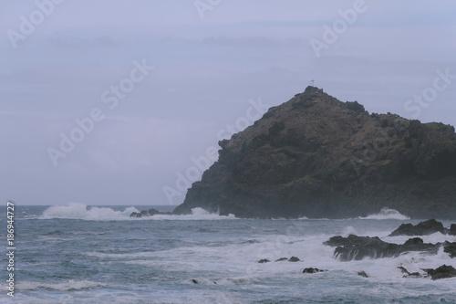 In de dag Kust Breaking waves on coastline in dark cloudy weather