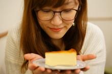 チーズケーキを持つ女性