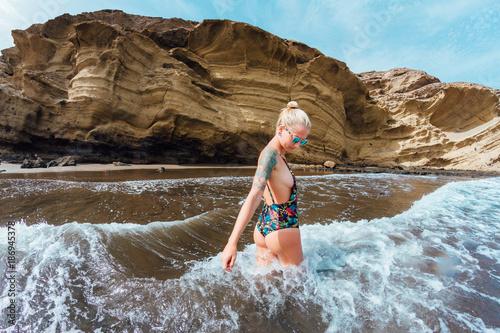 Tuinposter Canarische Eilanden Young blonde girl in thongs posing on sand beach in desert