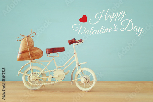 Fotobehang Fiets Valentine's day romantic background with white vintage bicycle toy and heart on it over wooden table.