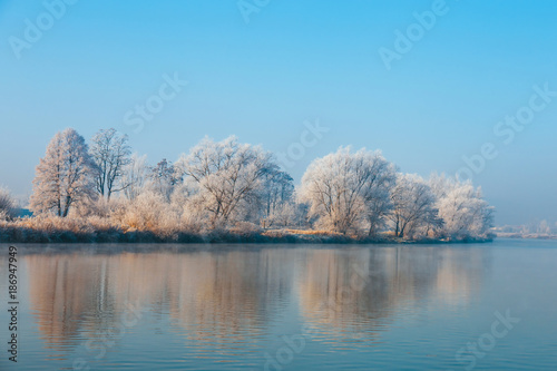 Foto op Aluminium Blauw winter landscape with a river and trees covered with hoarfrost