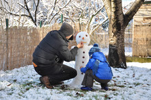Father And Son Make A Snowman ...