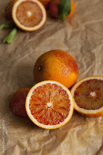 Whole and sliced blood orange on crumpled brown paper