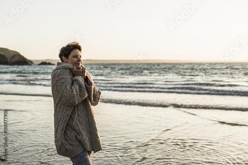 France, Crozon peninsula, woman wearing a cardigan on the beach at sunset