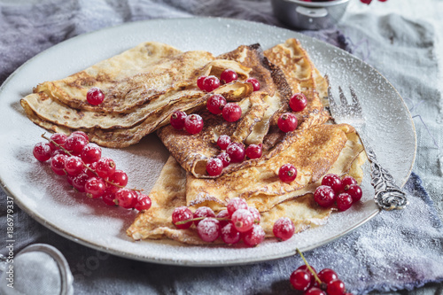 Crepes with red currents sprinkled with icing sugar on plate, close-up