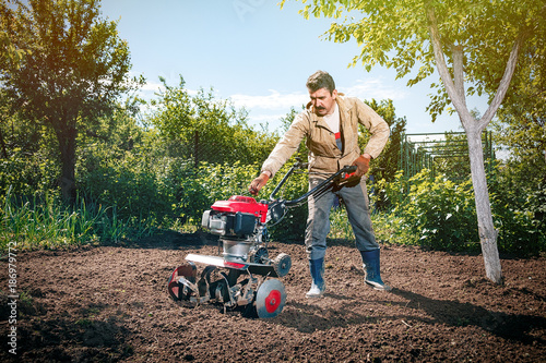 In de dag Afrika Happy man Farmer plows the land with a cultivator, preparing it for planting vegetables, on a sunny day garden
