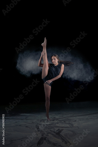 The girl gymnast makes a gymnastic sketch with flying powder. Sport. Dance.