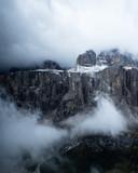 Chmury wirujące wokół wysokich skalistych szczytów i skał w górach w złej, nastrojowej pogodzie podczas burzy - 186981174