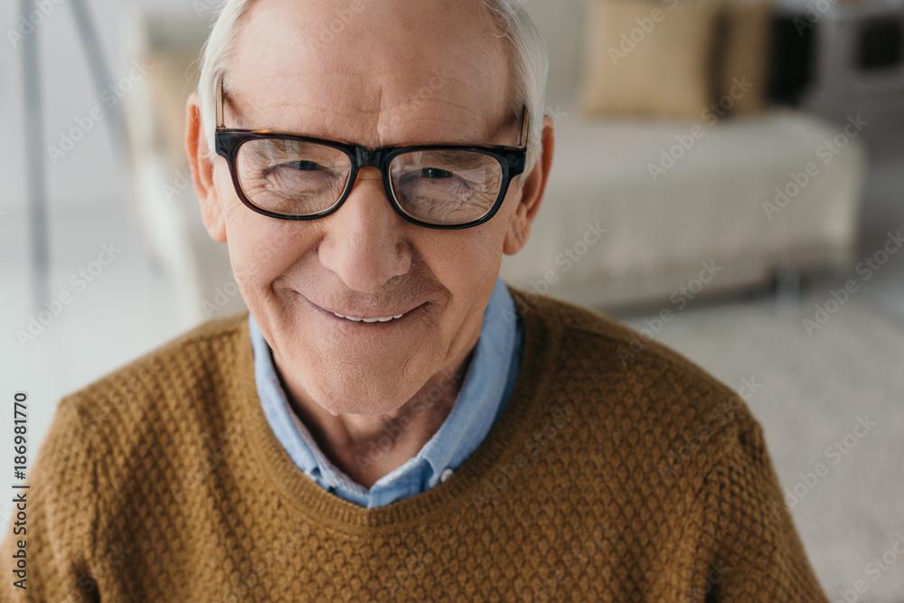 Fototapeta Senior smiling man wearing eyeglasses and looking at camera