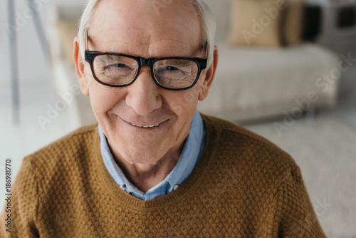 Fototapeta Senior smiling man wearing eyeglasses and looking at camera obraz