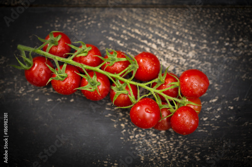 Bunch tomatoes on dark wood