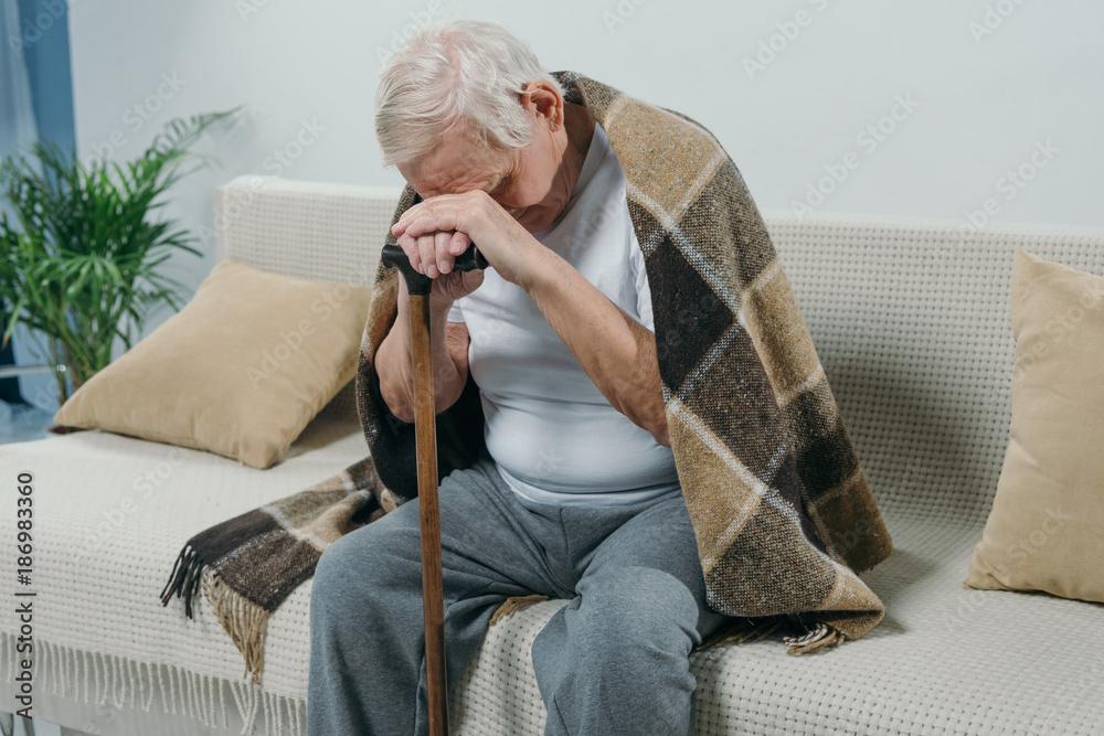 Fototapeta Tired senior man wearing plaid leans on a cane while sitting on sofa