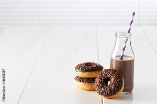Glass bottle of cocoa and three doughnuts with chocolate icing on white ground