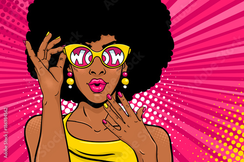 Wow pop art face. Sexy surprised black woman with african hair and open mouth holding sunglasses in her hand with inscription wow in reflection. Vector bright background in pop art retro comic style.