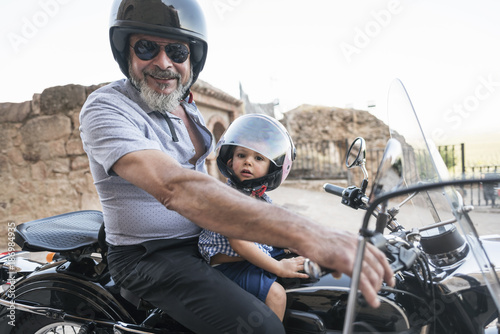 Grandfathers on sidecar bike with grandson in sunset family life scene. Jaen, Spain