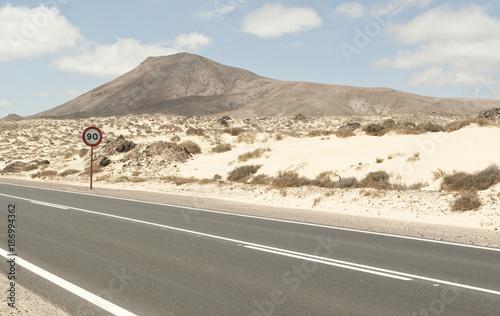 Spain, Fuerteventura, Corralejo, Parque Natural de Corralejo, view of empty road and road sign