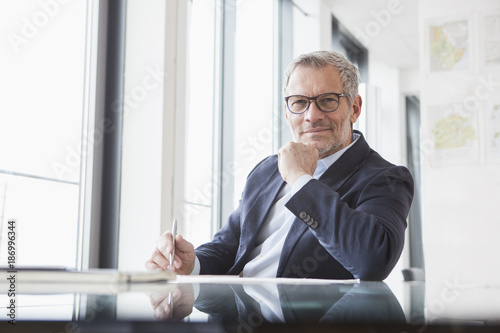 Successful businessman sitting at desk in his office