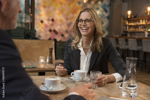 Happy businesswoman sitting in a restaurant with colleague