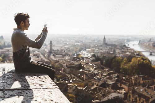 Italy, Verona, tourist photographing with smartphone
