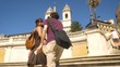 Happy young Couple tourists Walking on Piazza di Spagna Stairs in Rome holding hands on beautiful sunny summer day man and girl with backpack slow motion steadycam