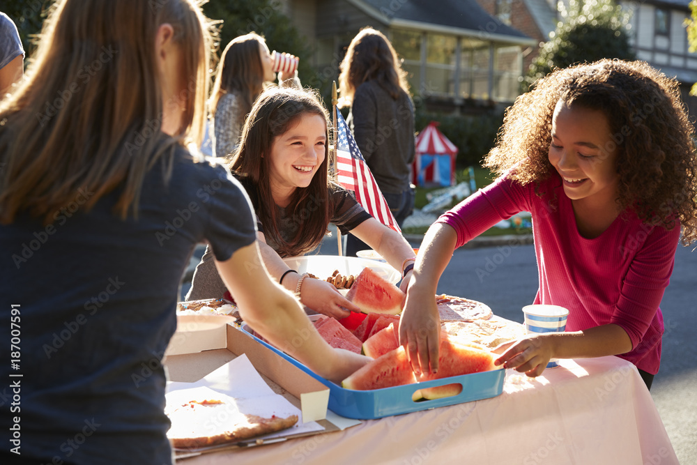 Fototapety, obrazy: Girls serving themselves watermelon at a block party