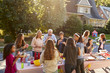 canvas print picture - Neighbours talk and eat around a table at a block party