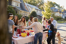 Neighbours Talk Standing Around A Table At A Block Party