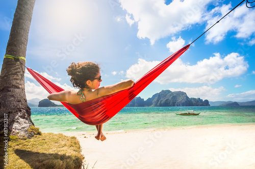Fotografia, Obraz  Young caucasian female relaxing in a red hammock on a tropical b