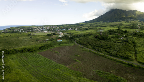 Aerial shot of town and farms at the foot of a volcano on St Kitts.
