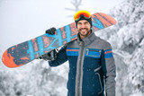 Man holding snowboard on ski terrain