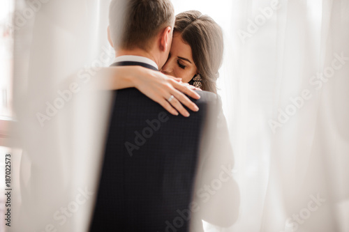 Stampa su Tela couple in love - bride and groom - gently embracing on a white background