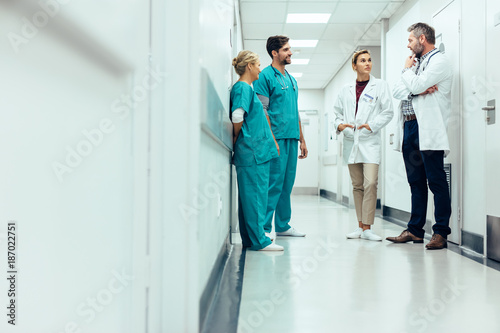 Fotografia  Team of doctors having discussion in hospital corridor