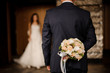 canvas print picture - groom keeping behind a bouquet of roses waiting for bride