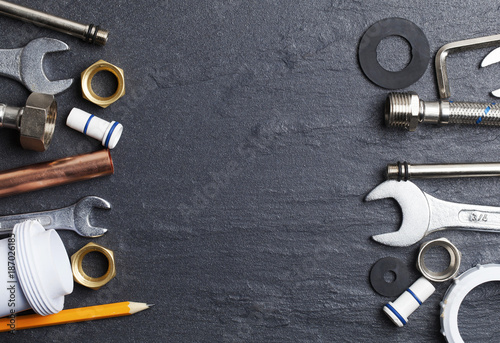 Fototapeta Plumbing concept. tools and pipes on a dark slate bakground obraz na płótnie