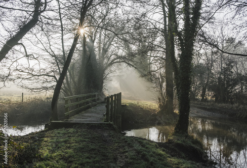 Sunlight through mist and fog over an old wooden footbridge. Nor Poster