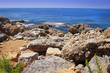 Landscape of rocky beach on blue sea. Scenery seascape on bright sunny summer day on tropical nature. Stones, rocks at coastline
