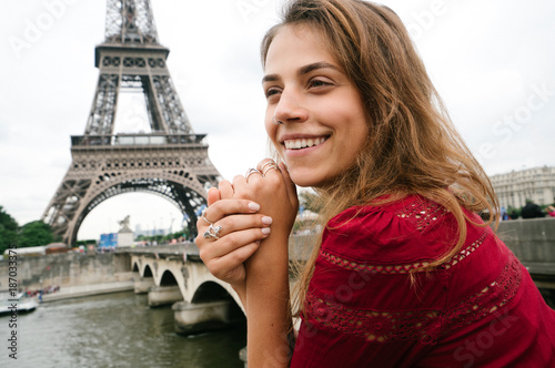 Young smiling woman in a red dress and Eiffel tower - 187033375