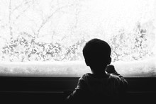 Little Kid Looking Out The Window On A Snowy Day