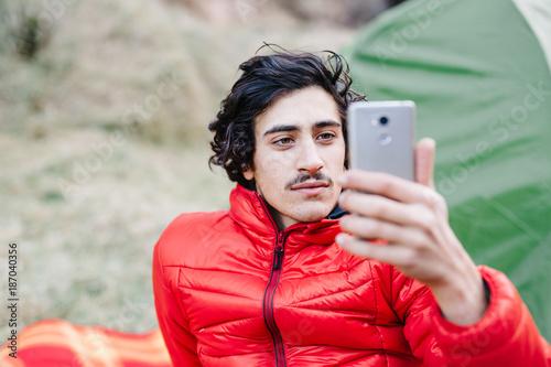 Man using phone in camp