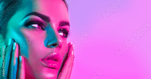 Poster Beauty Fashion model woman in colorful bright lights with trendy makeup and manicure posing in studio over purple background