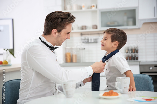 Photographie Young father helping his little son to knot necktie at home