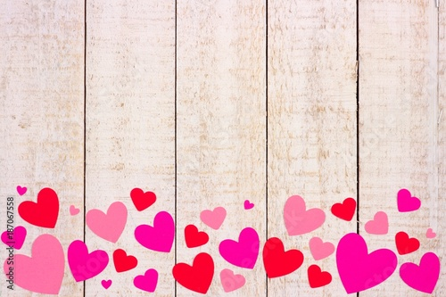 Valentines Day Bottom Border Of Red And Pink Paper Hearts Against A Rustic White Wood Background