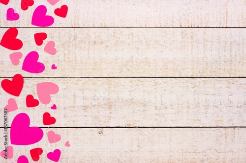 Valentines Day Side Border Of Red And Pink Paper Hearts Against A Rustic White Wood Background
